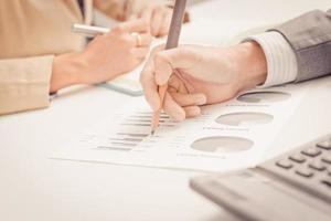 empresários discutindo as tabelas e gráficos mostrando os res foto