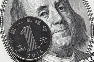 uma moeda chinesa yuan e nota de cem dólares foto