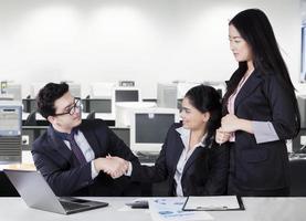 empresários, apertando as mãos na sala de escritório foto