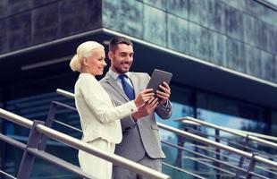 empresários sorridentes com tablet pc ao ar livre