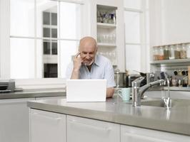homem maduro com laptop na cozinha