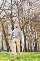 senhor idoso com muletas, caminhando no parque