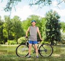 ciclista sênior posando por uma lagoa em um parque foto