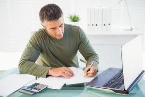 homem trabalhando com laptop e escrevendo foto