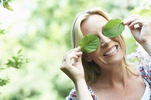 mulher sorridente, brincando com folhas foto