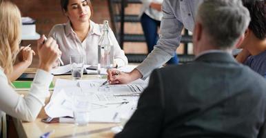 arquitetos trabalhando em planos na mesa da sala de reuniões de negócios foto