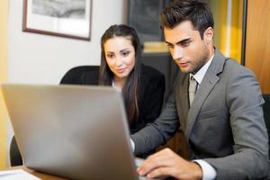 dois jovens parceiros de negócios discutindo planos ou idéias na reunião foto