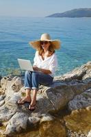 mulher com laptop à beira-mar foto
