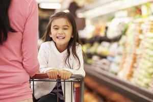 close-up da mãe empurrando filha feliz em um carrinho de loja foto