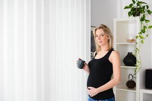 alegre mulher grávida madura em pé em casa bebendo chá foto
