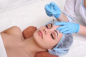 mulher bonita recebe uma injeção na cara dela. foto