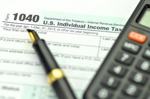 close de nós formulário de imposto, caneta e calculadora foto