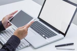 mão de homem trabalhando em tablet com fundo de computador. tecnologia. foto