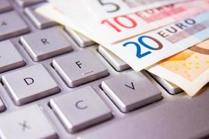 notas de euro em um teclado de computador foto