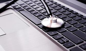 estetoscópio descansando em um teclado de computador - conceito para online foto