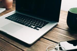 local de trabalho com o laptop aberto na mesa de madeira moderna foto