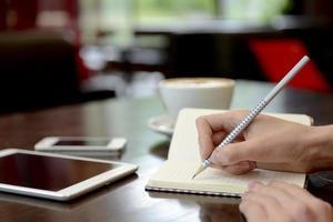 escrevendo em um caderno durante o trabalho foto