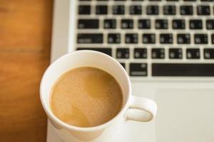 xícara de café com leite quente e laptop sobre fundo de madeira e textura. foto
