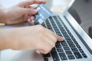 mãos segurando um cartão de crédito e usando o computador portátil