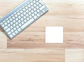 teclado de metal e bloco de notas branco em branco na mesa de madeira foto