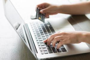 mãos segurando um cartão de crédito e usando o computador portátil foto