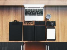 laptop de design genérico em cima da mesa de madeira com objetos de negócios foto