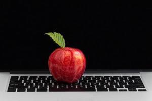 maçã vermelha fresca em cima do teclado do laptop foto