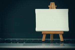 tela em branco e cavalete de madeira no computador portátil como conceito foto
