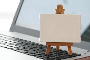 tela em branco e cavalete de madeira no computador portátil foto