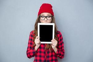 mulher assustada, cobrindo o rosto com computador tablet foto