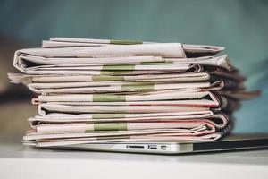 pilha de jornais, colocados em um laptop foto