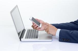 mãos de empresário, segurando o telefone móvel com o computador portátil