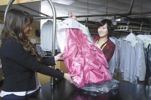 cliente coletando vestido limpo do proprietário na lavanderia