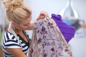 designer de moda sorridente, vestido de fixação no manequim em um estúdio foto
