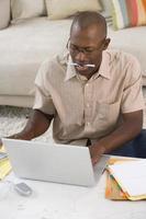 homem com caneta na boca no computador portátil, vista elevada foto