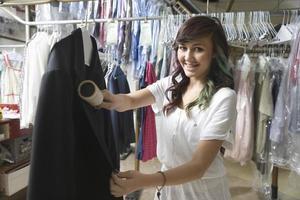mulher escovando o casaco na lavanderia foto