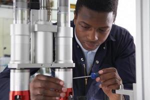 Engenheiro aprendiz masculino trabalhando na máquina na fábrica foto