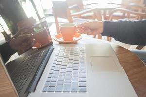 espaço de trabalho com laptop e xícara de café na mesa de madeira foto