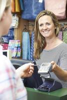 comprador que paga por mercadorias usando a máquina de cartão de crédito foto