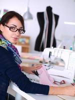 jovem costura enquanto está sentado no seu local de trabalho foto