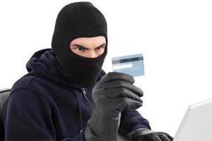 ladrão usando cartão de crédito e laptop