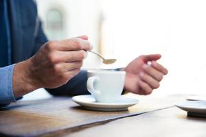 mãos do empresário com café foto