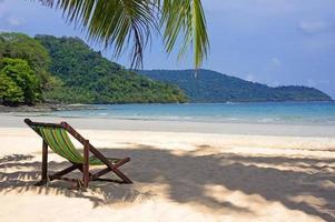 praia tropical. cadeiras de praia na praia de areia branca foto