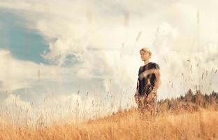 jovem desfrutar com brisa suave no campo dourado foto