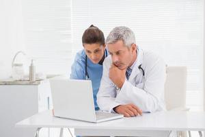médicos olhando para laptop foto