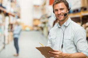 gerente de armazém usando fone de ouvido escrevendo na área de transferência foto