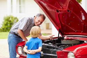 avô e neto trabalhando no carro clássico restaurado