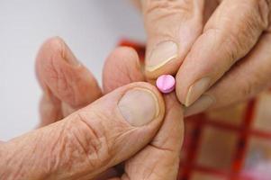 mãos idosas segurar um comprimido rosa entre os dedos foto
