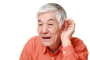 homem japonês sênior com a mão atrás da orelha, ouvindo atentamente