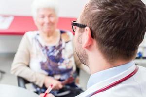 médico vendo paciente sênior na prática foto